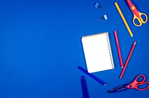 Forniture scolastiche differenti colorate su fondo di carta blu. Foto Premium