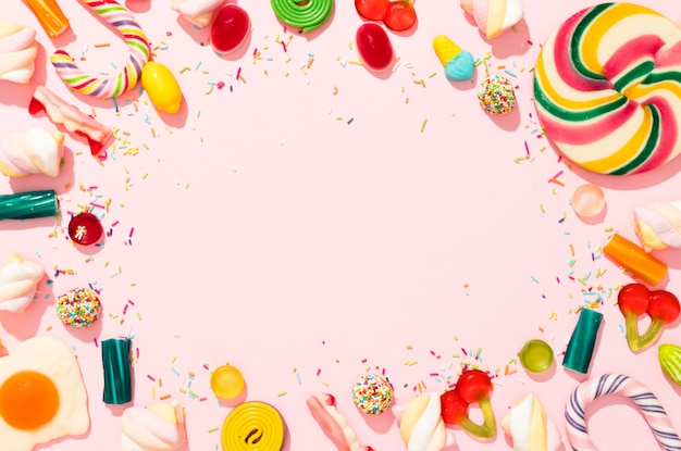 Composizione di caramelle colorate su sfondo rosa con spazio di copia Foto Premium