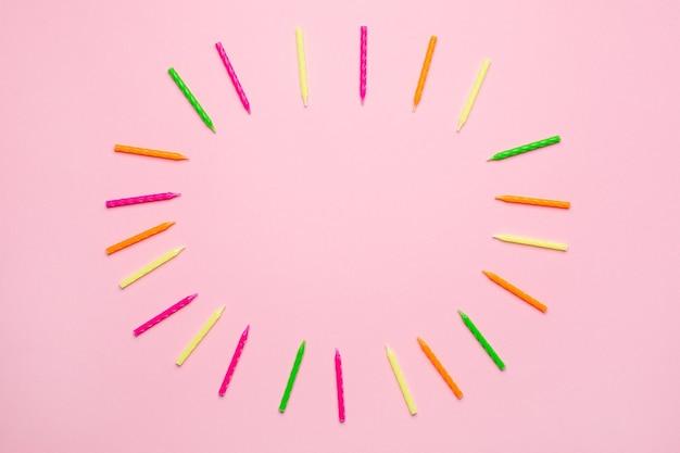 Candele colorate per cornice torta di compleanno su sfondo rosa Foto Premium