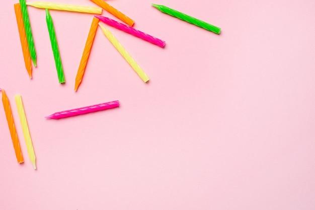 Candele colorate per torta di compleanno su uno sfondo rosa Foto Premium
