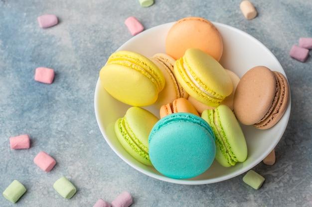 Biscotti colorati macarons sul piatto e marshmallow ariosi Foto Premium