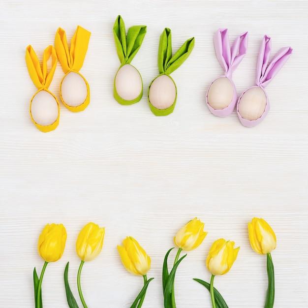 Uova di pasqua colorate con orecchie di stoffa come coniglietto di pasqua. tulipano di fiori di primavera giallo brillante Foto Premium