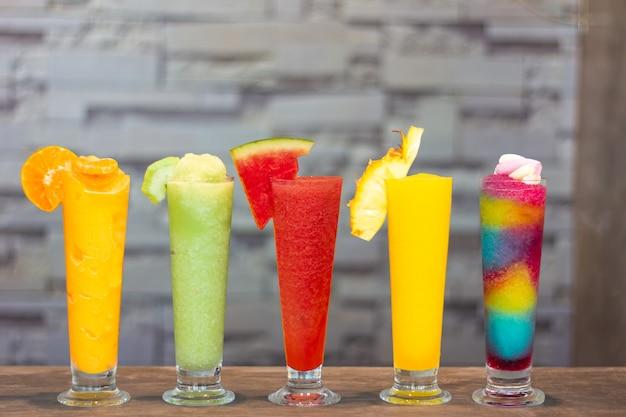 Frullati freschi colorati con frutta tropicale su sfondo grigio Foto Premium