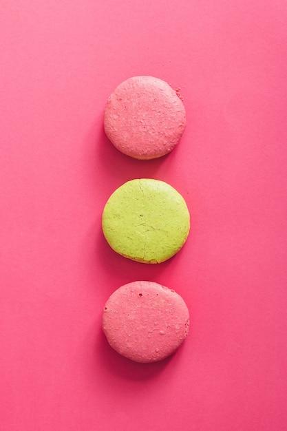 Amaretti colorati torte sulla parete rosa. lay piatto. Foto Premium