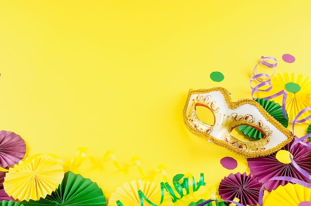 Coriandoli di carta colorati, maschera carnivale e serpentina colorata su sfondo giallo Foto Premium