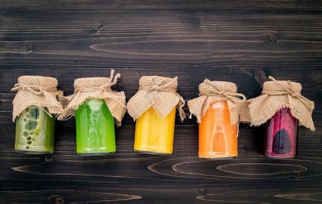Frullati e succhi sani variopinti in bottiglie con frutta tropicale e superfoods freschi su fondo di legno. Foto Premium