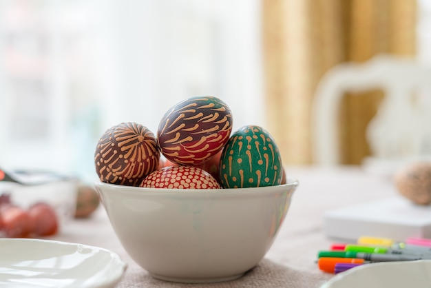 Uova di pasqua dipinte di cera colorata nella ciotola sulla tavola di legno Foto Premium