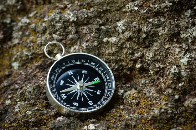 Bussola posta sulla roccia nella foresta. primo piano e copia spazio. concetto di viaggio avventura nella giungla. Foto Premium