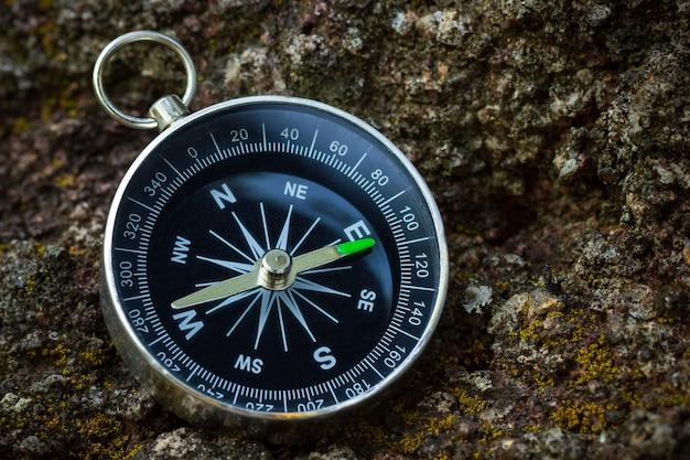 Bussola posta sulla roccia nella foresta. primo piano e copia dello spazio. concetto di viaggio avventura nella giungla. Foto Premium