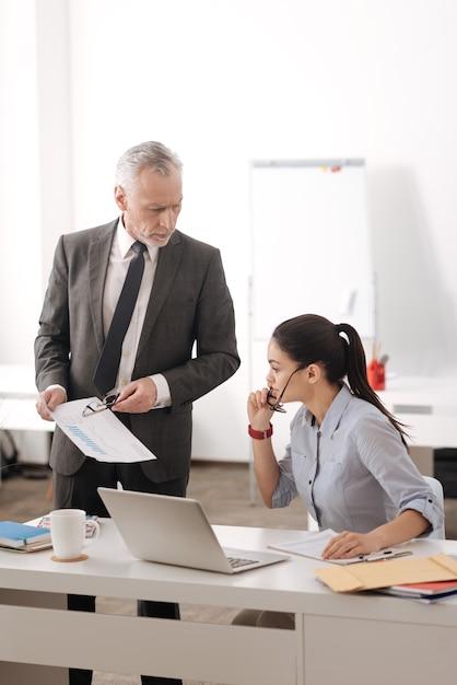 Giovane donna competente che tiene gli occhiali nella mano destra, mettendo la mano sinistra sul tavolo mentre guarda i documenti Foto Premium