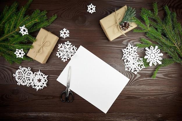 Composizione per tagliare i fiocchi di neve di carta sulla tavola di legno Foto Premium