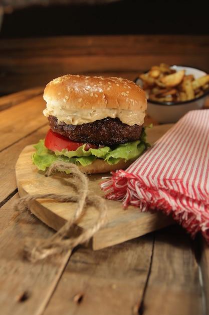 Composizione di hamburger rustico con patatine fritte Foto Premium