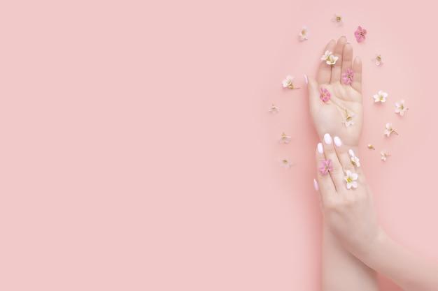 Bellezza di concetto. cosmetici naturali per le mani con estratto di fiori. mano di donna moda estate Foto Premium