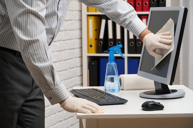 Concetto di pulizia o disinfezione dell'ufficio: un uomo d'affari pulisce il posto di lavoro, il computer, la scrivania, utilizza una pistola a spruzzo e tovaglioli di carta. pulizia delle superfici da microbi, virus e sporco. Foto Premium