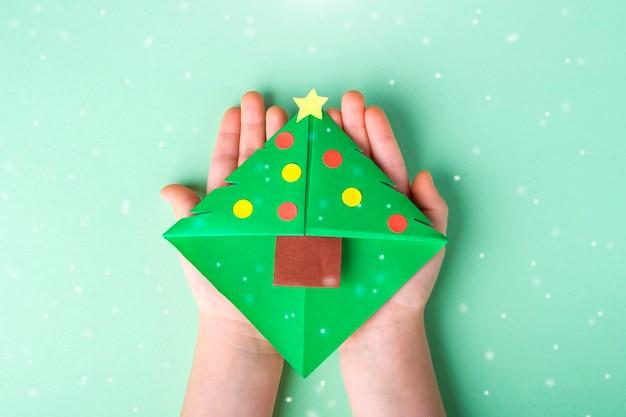Concetto di fai da te e creatività per bambini, origami. segnalibro della holding della mano del bambino come albero di natale. Foto Premium