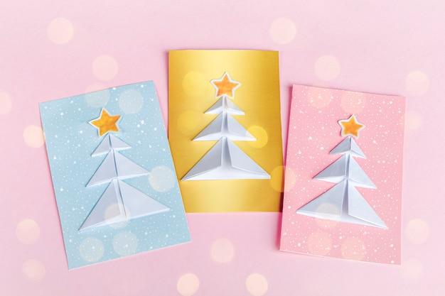 Concetto di fai da te e creatività per bambini, origami. crea biglietti di auguri blu, rosa e dorati con origami di alberi di natale Foto Premium