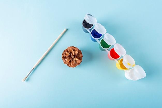 Concetto di fai da te e creatività per bambini. istruzioni passo passo: dipingere la pigna. strumenti del passaggio 1: cono, pennello, vernice. artigianato natalizio per bambini Foto Premium