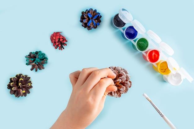 Concetto di fai da te e creatività per bambini. istruzioni passo passo: dipingere la pigna. fase 2 le mani del bambino dipingono la pigna con vernice bianca. artigianato natalizio per bambini Foto Premium