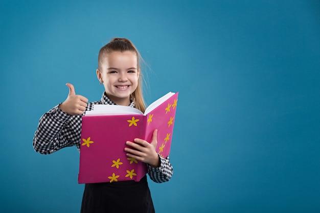 Concetto - educazione. ragazza che legge un libro in una copertina rosa Foto Premium