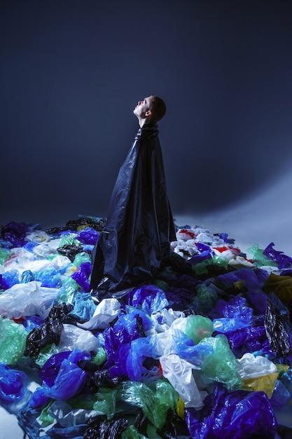 Concetto con problemi ecologici, prova dell'inquinamento, isolato sulla parete scura dello studio. giovane in studio, circondato da sacchetti di immondizia di plastica vuoti. Foto Premium