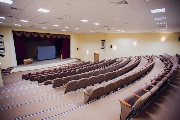 Sala riunioni per conferenze con luci a led a soffitto, sedie marrone fila, con palcoscenico e schermo vuoto per riunioni d'affari, conferenze Foto Premium