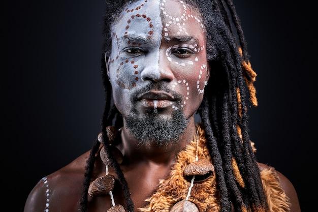 Fiducioso aborigeno africano isolato sopra il muro nero, con disegni etnici colorati sul viso Foto Premium
