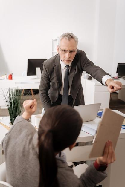 Impiegato fiducioso in piedi vicino al suo posto di lavoro alzando il braccio sinistro mentre guarda il suo manager Foto Premium