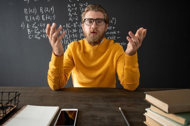 Fiducioso insegnante di algebra che spiega il nuovo argomento ai suoi studenti online mentre è seduto a tavola con libri e blocco note davanti alla telecamera Foto Premium