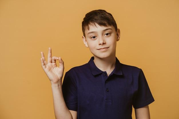 Fiducioso giovane ragazzo con gli occhi marroni vestito con una maglietta blu scuro, mostra il gesto giusto, essendo di buon umore, fa la scelta migliore. concetto di salute, educazione e persone. Foto Premium