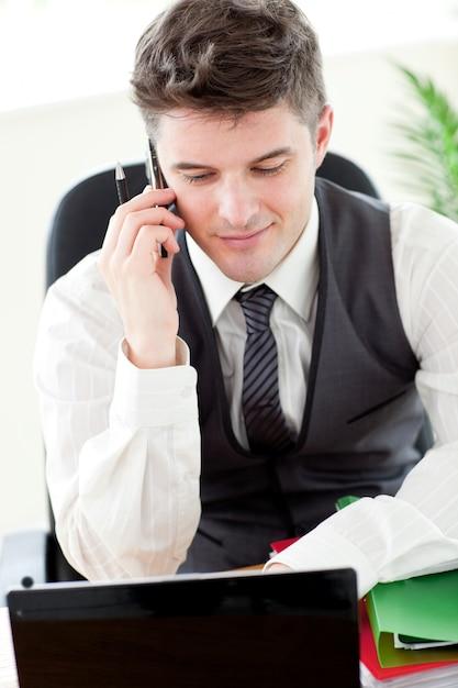 Giovane uomo d'affari sicuro che comunica sul telefono Foto Premium