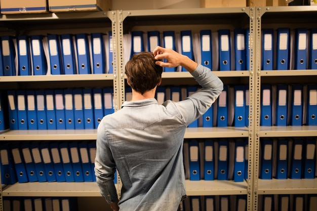 Uomo d'affari confuso alla ricerca di file sull'armadio nel ripostiglio Foto Premium