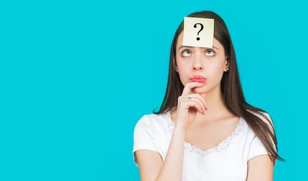 Pensiero femminile confuso con il punto interrogativo sulla nota adesiva sulla fronte. Foto Premium