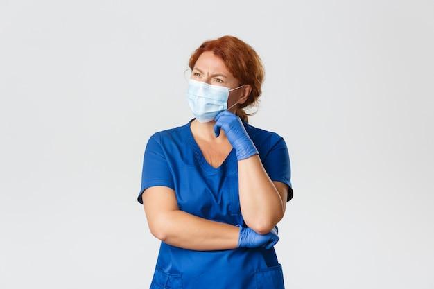 Dottoressa rossa confusa e premurosa, infermiera in camice, maschera per il viso e guanti pensando, distogliendo lo sguardo indeciso, facendo una scelta o una decisione. Foto Premium