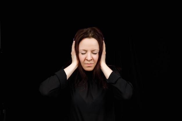 Donna confusa tenendo le mani sulla testa su sfondo nero per studio. ritratto di giovane ragazza seria chiudendo le orecchie, non sento il male, concetto di sordità, copia dello spazio. Foto Premium