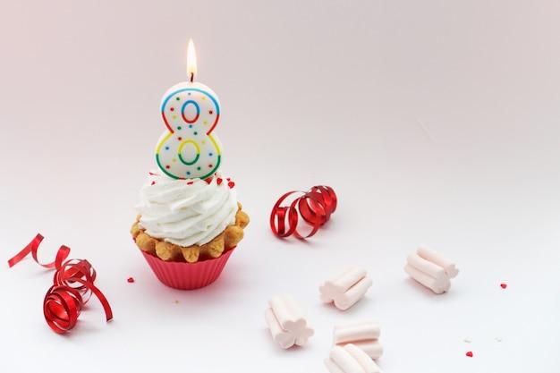 Congratulazioni per la giornata internazionale della donna l'8 marzo, torta alla crema e il numero otto su sfondo bianco Foto Premium