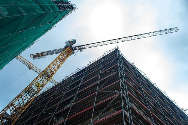 Gru a bandiera da cantiere. costruzione di nuovi edifici moderni. architettura urbana. Foto Premium