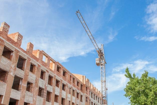 Cantiere di un nuovo edificio alto appartamento con gru a torre contro il cielo blu. sviluppo dell'area residenziale. Foto Premium