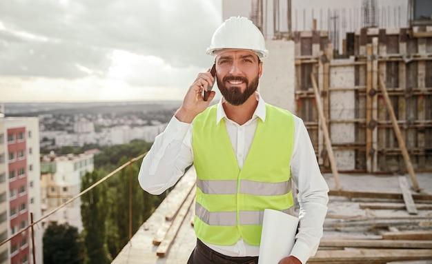 Operaio edile rispondendo alla telefonata in loco Foto Premium