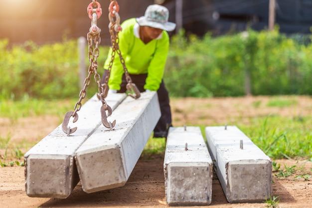 Muratore che scarica il palo concreto dal camion Foto Premium