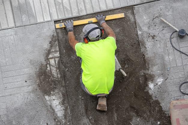 Operaio edile con livello di costruzione che lavora su un marciapiede. concetto di manutenzione Foto Premium