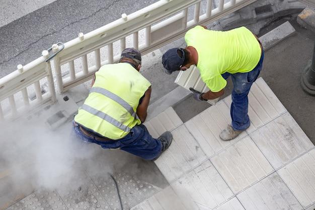 Lavoratori edili che riparano un marciapiede. concetto di manutenzione Foto Premium