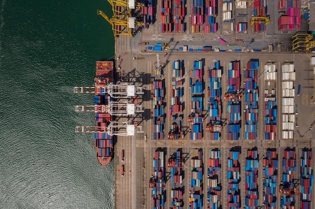Carico e scarico della nave porta-container nel porto marittimo, vista aerea del trasporto di merci di importazione ed esportazione logistica aziendale tramite nave portacontainer nel porto, nave da carico di carico Foto Premium