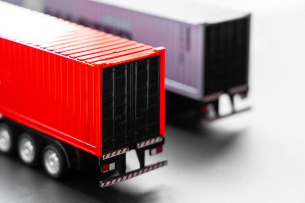 Fuoco selettivo del camion del contenitore su fondo bianco, parcheggio del camion del contenitore del rimorchio al magazzino, logistica di affari globali e compagnia di spedizioni dei trasporti. Foto Premium