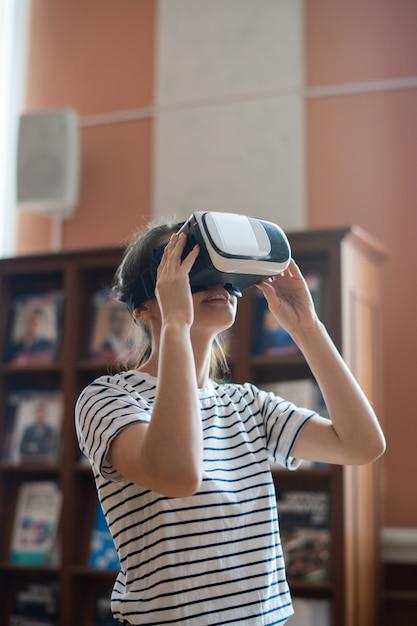 Ragazza adolescente contemporanea con auricolare vr guardando il display virtuale mentre si guarda un film in 3d nella biblioteca del college Foto Premium
