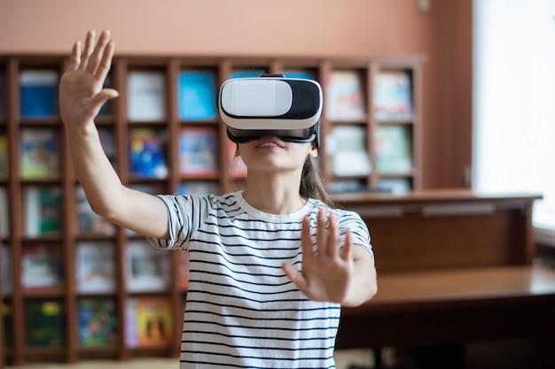 Ragazza adolescente contemporanea con auricolare vr toccando il display virtuale mentre si prepara la presentazione nella biblioteca del college Foto Premium
