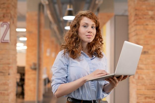 Contenta giovane donna sicura di sé con i capelli rossi ricci in piedi nello spazio di co-working loft e utilizzando il computer portatile Foto Premium