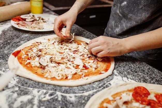 Cuocere in cucina mettendo gli ingredienti sulla pizza. concetto di pizza. produzione e consegna di cibo. Foto Premium