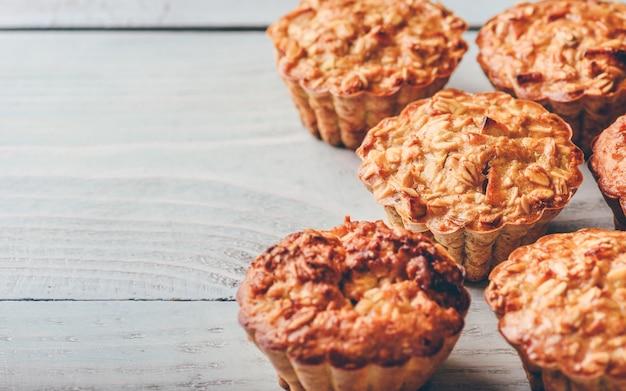 Muffin di farina d'avena cotta su fondo di legno chiaro. Foto Premium