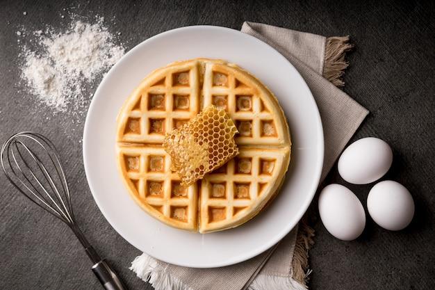 Cucinare deliziosi waffle con dolce nido d'ape, frusta in acciaio, uova - sfondo di pietra, stile scuro Foto Premium