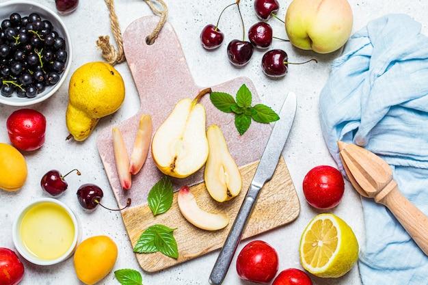 Cucinare la macedonia. tagliare la frutta su una tavola, vista dall'alto. concetto di cibo vegano sano. Foto Premium